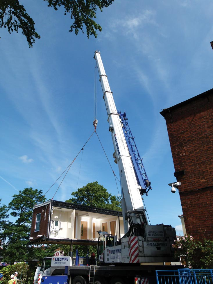 Mobile crane lifting modular building